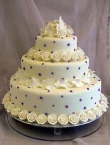 Three tier round white wedding cake with purple dots and white flowers.JPG
