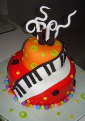Two tier orange and red cake with piano keyboard.JPG