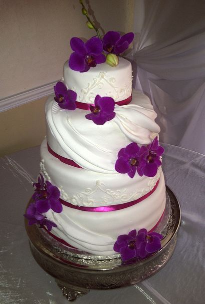 Four tier white wedding cake with purple flower petals and red bandsg mightylinksfo