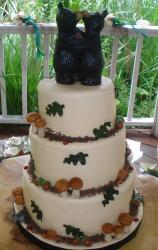 Three tier round white outdoor theme wedding cake with kissing bears topper and mushrooms and snails.JPG