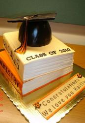 Graduation cake with two textbooks and graduation cap on top.JPG
