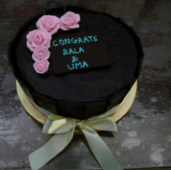Black engagement cake with pink flowers and letters.PNG