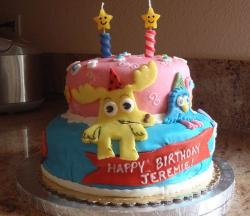 Two tier round pink and bue second birthday cake with smiling star candles.JPG