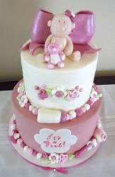 2 tier white and pink baby shower cake for baby girl with pink bow and baby on top.JPG