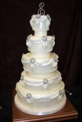 5 tier round white wedding cake with drapes and crystal monogram topper.JPG
