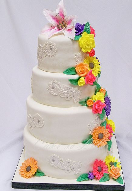 Four tier round white wedding cake with lily on top and other colorful flowers draping down.JPG