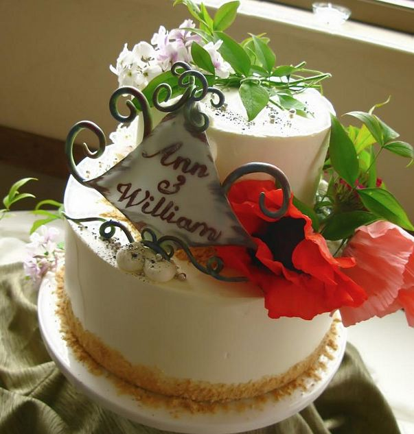 Two Tier Round White Wedding Cake With Fresh Leaves And Flowers JPG