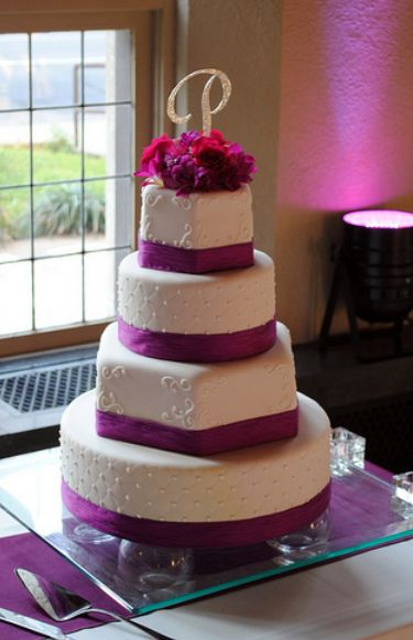 four tier round and hexagonal white wedding cake with magenta bands and flowers and crystal