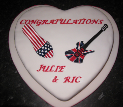 Heart shaped engagement cake with guitar and shoe theme.PNG