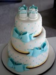 Three tier round white baby shower cake with little boots on top and powder blue bows.JPG