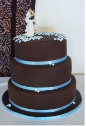 Chocolate wedding cake with blue ribbons_bride and groom making out cake topper.PNG