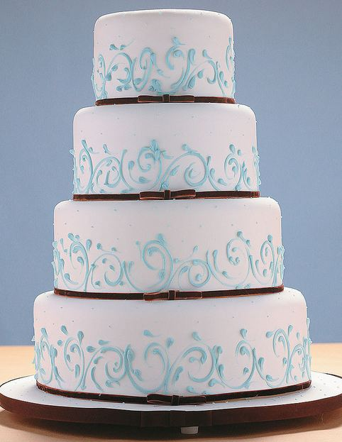 Four Tier Round White Wedding Cake With Thin Brown Bands At Base And Light Blue TouchesJPG