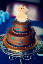 Double tier chocolate baby shower cake with smiling baby on top.JPG