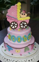 2 tier pink round baby shower cake for baby girl with carriage on top.JPG
