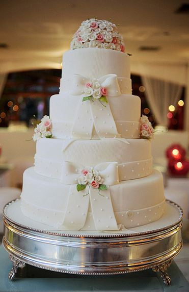 Round white four tier wedding cake with two white ribbons and pink and white mini rose toppers.JPG