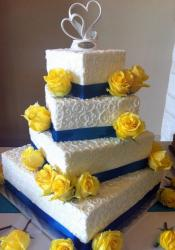 Four tier white offset rectangular wedding cake with blue bands and yellow roses.JPG