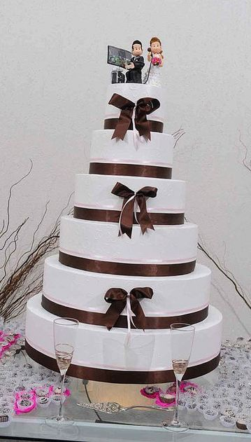 Six tier round white wedding cake with brown bows and bride and groom toppers.JPG