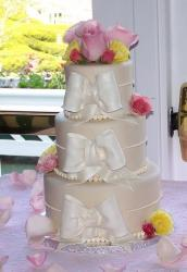 3 tier round beige wedding cake with pink flowers on top and white bows.JPG