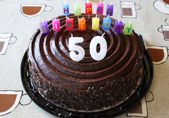 Round Chocolate 50th Birthday Cake With Colorful Candles Spelling Out Happy BirthdayJPG