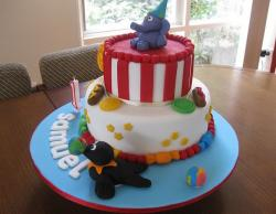 Two tier first birthday cake with elephant and seal and corndogs.JPG