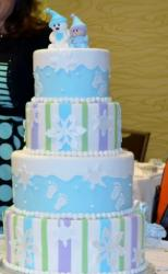 4 tier baby-shower cake with snowflakes footprints & cute toppers with beanie hats.JPG