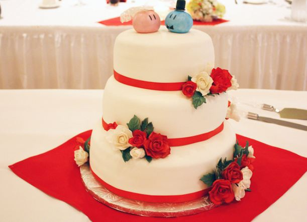 3 tier round white wedding cake with red bands and fresh roses and ball-shaped bride and groom topper.JPG