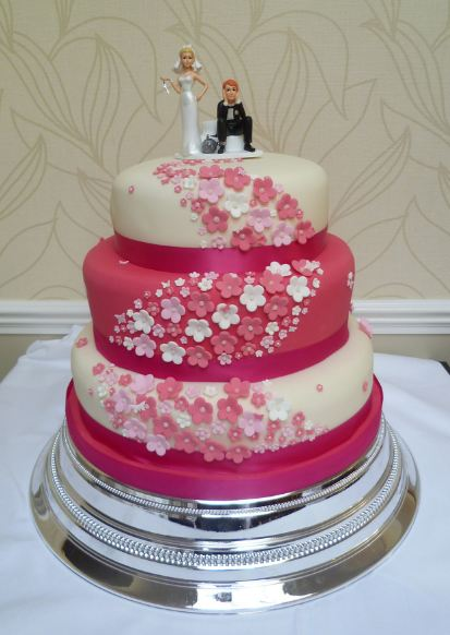 Three tier pink and white round wedding cake with bride and groom ...