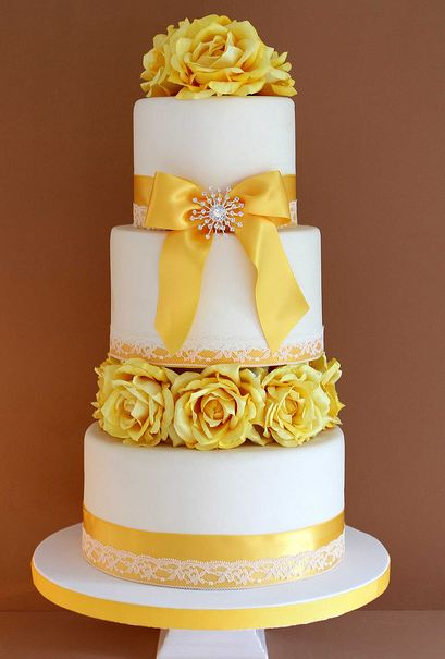 Three tier round white wedding cake with yellow flowers and ribbons