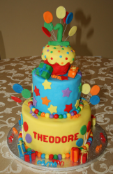 Beautiful big first birthday cake with balloons and gifts theme in many different bright colors.PNG