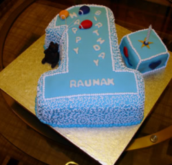 Boy first birthday cake with number 1 cake shape in blue with a toy box cake on the side.PNG