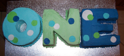 One words first birthday cake for baby boy with color theme of blue and green and some white.PNG