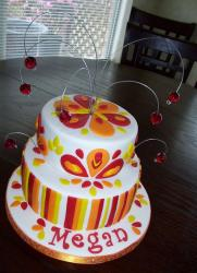Two tier white round birthday cake with woman with stripes and red crystals.JPG