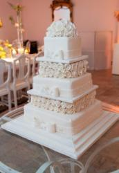 Five tier square wedding cake in white with faux white roses as second and fourth tiers and topper.JPG