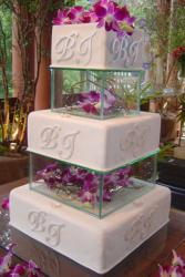 Five tier white monogramed square wedding cake with second and fourth tiers in glass with flowers inside.JPG