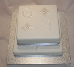 Silver monogrammed engagement cake in square shape.PNG