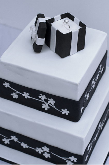 Square white and black engagement cake with engagement ring in gift box.PNG
