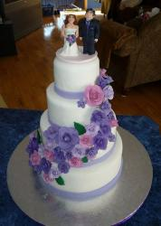Four tier round white wedding cake with cascading purple and pink flowers and bride and groom toppers.JPG