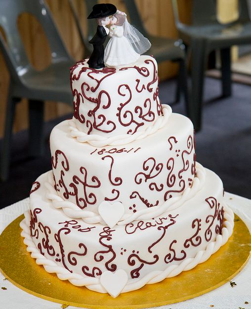 Three Tier Heart Shaped White Wedding Cake With Groom And Bride Topper JPG