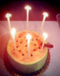 Melon birthday cake with candles.JPG