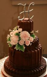 Four tier round chocolate wedding cake with monogram topper and fresh flowers.JPG