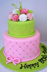 Two tier 80th birthday cake in green and pink with fresh flowers on top.JPG