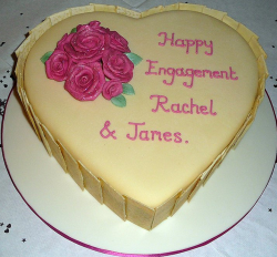 White chocolate engagement cake in heart shape with pink letters.PNG