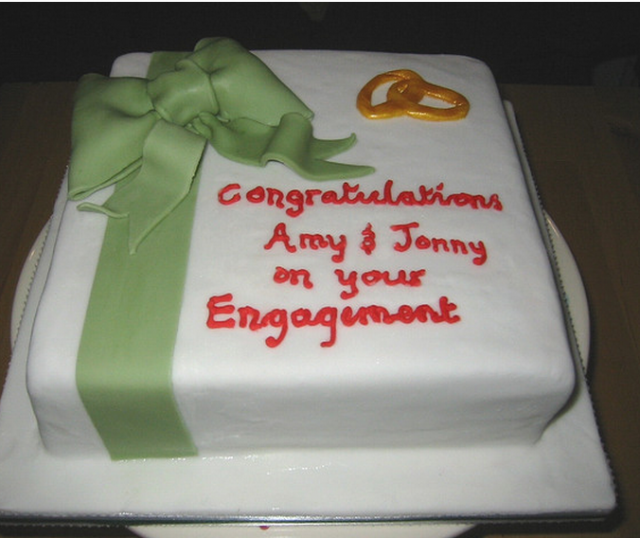 White square engagement cake with green bow with yellow gold rings with letters.PNG