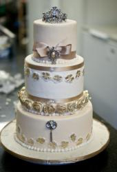 3 tier round white wedding cake with gold roses, pearls and crown on top.JPG
