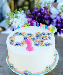 White round first birthay cake with mini flowers for girl.JPG