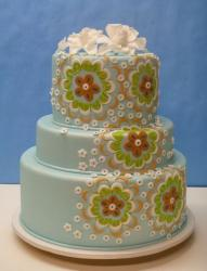 3 tier baby blue round wedding cake with floral patterns and white flowers on top.JPG