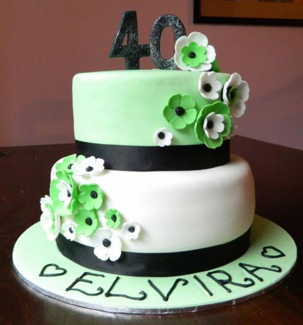Two tier round white 40th birthday cake with green and white flowers.JPG