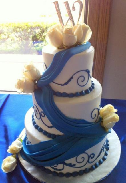 three tier round white wedding cake with blue drape and