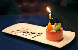 Orange round mini cake with kiwi and single candle.JPG