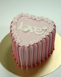 Heart-shaped cake with pink and red stripes with the word Love on top.JPG
